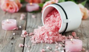Spa with pink salt, roses and candles, selective focus