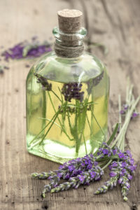 bottle of lavender oil with fresh flowers on wooden background. apothecary herbs. selective focus