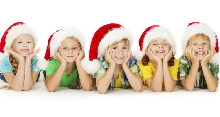 Group of happy Christmas kids in Santa hat lying down. White background.