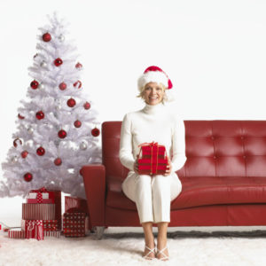 Young Woman Sitting on Couch Holding Christmas Present and Wearing Santa Hat --- Image by © Royalty-Free/Corbis