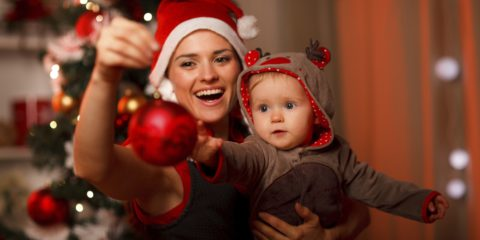Happy mother showing Christmas ball  to baby near Christmas tree