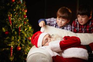 Cute siblings looking at Santa Claus sleeping by xmas tree, one of them touching him
