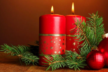 Two candles and christmas decorations, on brown background