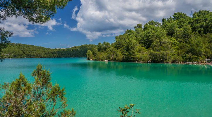 Clean, clear turquoise green lake water surrounded by trees and Mediterranean vegetation. Blue sky with beautiful white clouds.